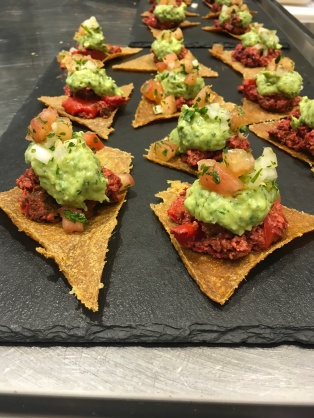 Tortilla crisps made with raw maize loaded with a smoked aubergine meat and guacamole